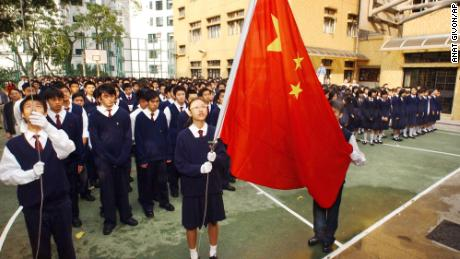 Students at the patriotic Heung To Middle School in Hong Kong watch as Cheung Kit-yuk, center, and Chiu Pak-min, far left,  raise the Chinese national flag to the sounds of the national anthem during a ceremony in the school grounds, Friday, April 2, 2004.