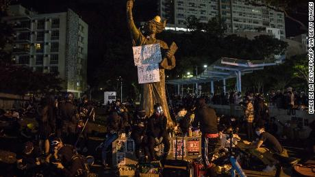 Protesters sit next to a Goddess of Democracy statue at the Chinese University of Hong Kong (CUHK) in Hong Kong on November 12, 2019.