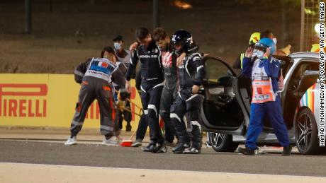 Stewards and medics attend to Romain Grosjean after the crash.