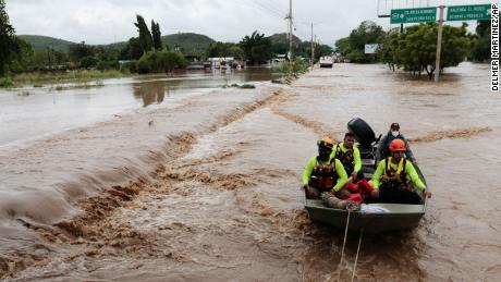 Rescuers navigate a flooded road in a boat after the passing of Hurricane Iota in La Lima, Honduras, Wednesday, Nov. 18, 2020.