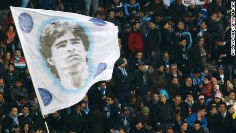 Fans of SSC Napoli wave a flag depicting former Argentine forward Diego Armando Maradona.