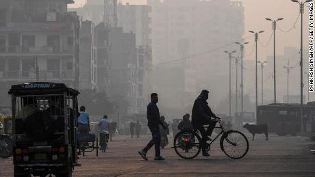 People make their way along a street amid smoggy conditions in New Delhi on November 15, 2020.