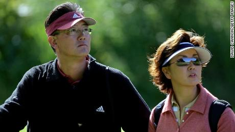 BJ Wie (left) and his wife Bo Wie watch their daughter during practice for the 2004 Curtis Cup Matches.