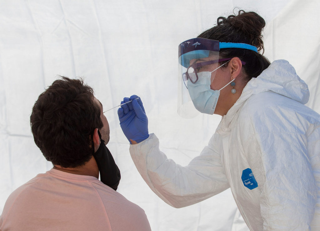 Lane County's Deputy Public Health Officer Dr. Lisandra Guzman uses a swab to collect a sample for a Covid-19 test at a site on Dec. 10, at Centro de Fe Church in Eugene, Oregon.