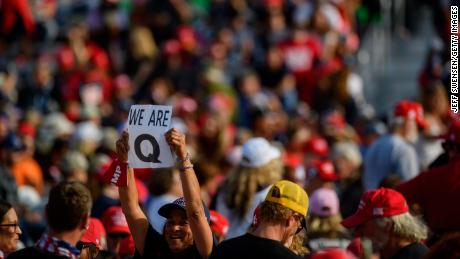 A woman holds up a QAnon sign to the media as attendees wait for President Donald Trump to speak at a campaign rally at Atlantic Aviation on September 22 in Moon Township, Pennsylvania.