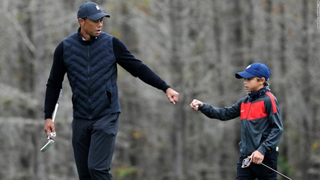 Tiger Woods warms-up with his son Charlie, 11, and the similarities are striking