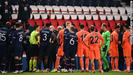 Romanian referee Ovidiu Hategan talks to Istanbul Basaksehir's staff members and players.