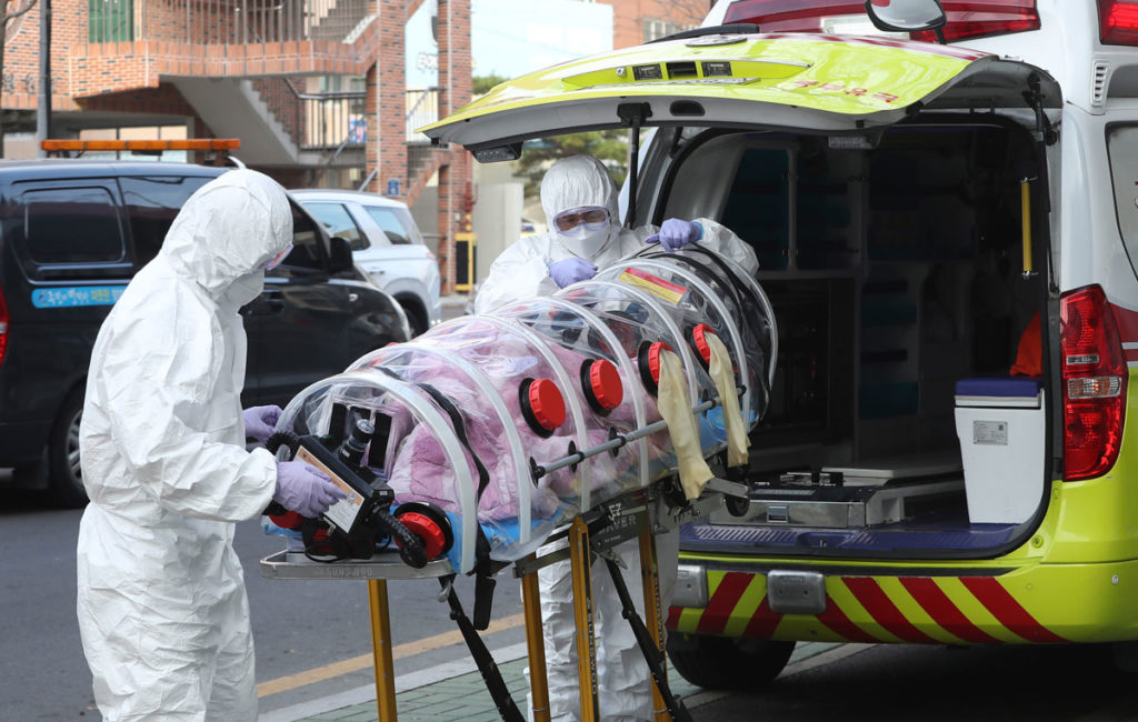 Medical workers hoist a patient infected with the coronavirus onto an ambulance in Ulsan, South Korea on Monday, December 7.