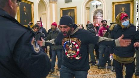 Trump supporters gesture to U.S. Capitol Police in the hallway outside of the Senate chamber