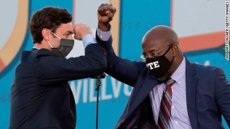 Jon Ossoff, left and Raphael Warnock bump elbows during a rally with US President-elect Joe Biden in Atlanta on January 4.