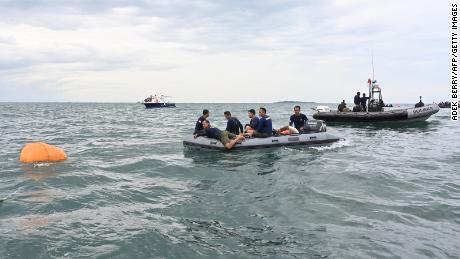 Navy divers use a flotation device to retrieve wreckage from the plane.