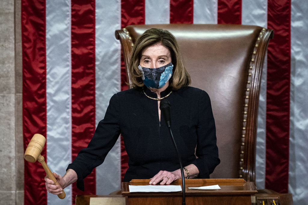 US House Speaker Nancy Pelosi, wears a protective mask while banging the Speaker's gavel on the floor of the House at the US Capitol in Washington, DC, on January 13.