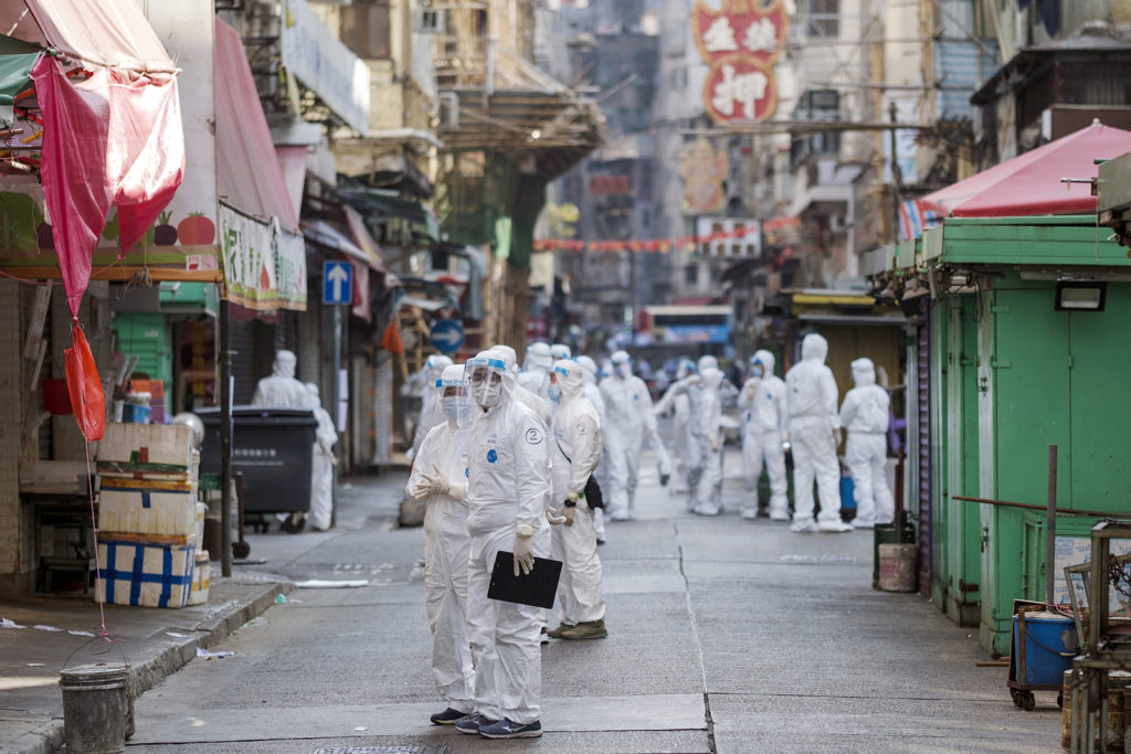 Government workers wearing personal protective equipment (PPE) work in an area under lockdown in the Jordan area of Hong Kong, on January 23.