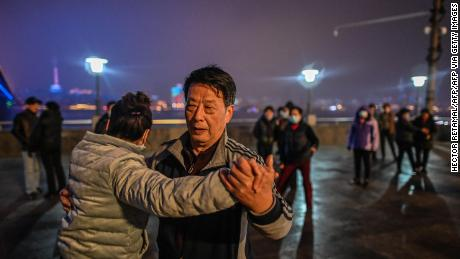 Elderly couples dance along the Yangtze River that cuts through the heart of Wuhan.