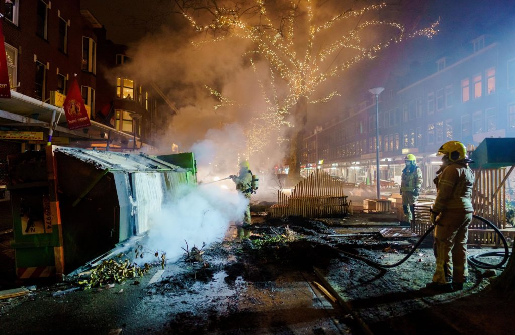 Firefighters work to extinguish a fire in Rotterdam on January 25, after a wave of riots in the Netherlands in response to a coronavirus curfew introduced over the weekend.
