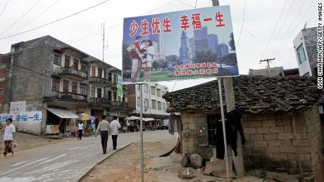 """A one-child policy billboard saying, """"Have less children, have a better life"""" greets residents on the main street of Shuangwang in southern China in 2007."""