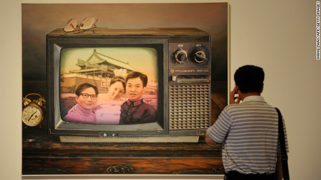 A man looks at a painting named 'Better To Have Only One Child' at the China National Art Museum in Beijing in 2012.