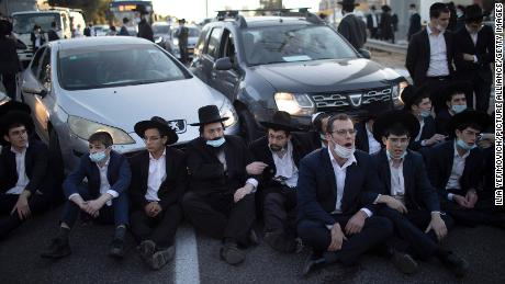 Ultra-Orthodox Jews block a road in Bnei Brak during a demonstration staged moments before Israel entered a thirdnationwide lockdown on December 27.