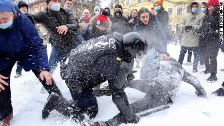 A policeman detains a man while protesters try to help him, during a protest in St. Petersburg on Sunday against the detention of opposition leader Alexey Navalny.