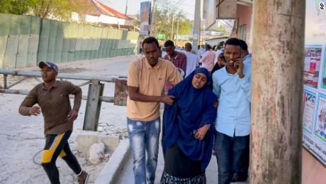 People flee as gunshots are heard on a street near the Afrik hotel in Mogadishu