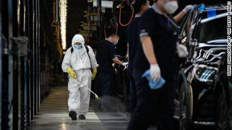 A cleaner wearing protective gear sprays disinfectant along a production line at an automotive plant in Beijing on May 13, 2020.