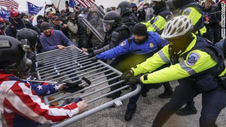 Supporters of President Donald Trump try to break through a police barrier at the US Capitol on January 6, 2021. (AP Photo/John Minchillo)