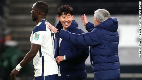 Jose Mourinho celebrates with Tottenham's two goalscorers at the final whistle.