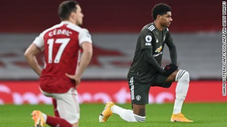 Marcus Rashford (R) takes a knee ahead of the match against Arsenal.