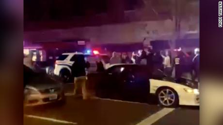 A still image from video of the incident shows people surrounding the vehicle.