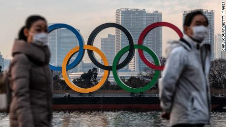 People wearing face masks walk past the Olympic Rings on January 22 in Tokyo.