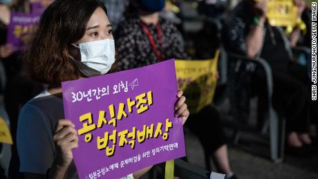 A woman holds a sign demanding a formal apology and compensation from Japan, at a rally marking the 2020 International Memorial Day for Comfort Women in Seoul, South Korea.