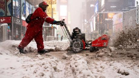 A worker clears snow off the sidewalks in Times Square, New York City, on Monday.