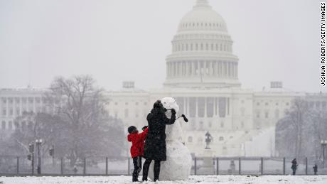Janine Iselmann and her son Max, build a snowman in Washington, DC, on Monday.