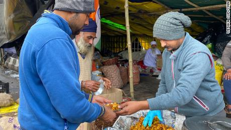 A farmer gives out food at the camp in Ghazipur, on February 4, 2021.
