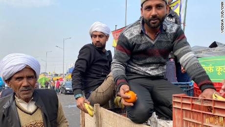 Farmers in Ghazipur gather fresh fruit from the back of a supply truck, on February 4, 2021.