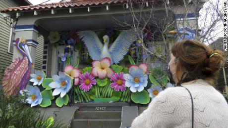 Designer Caroline Thomas looks at a house decorated like a parade float.