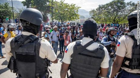 Journalists face armed police as they gather outside the Departmental Directorate of Police to file a complaint after they were hit with tear gas in Port-au-Prince, February 10, 2021.