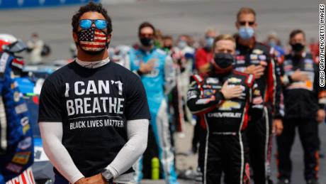"""Bubba Wallace wears a """"I Can't Breathe - Black Lives Matter"""" T-shirt under his fire suit in solidarity with protesters around the world taking to the streets after the death of George Floyd on May 25 while in the custody of Minneapolis, Minnesota police, stands during the national anthem prior to the NASCAR Cup Series Folds of Honor QuikTrip 500 at Atlanta Motor Speedway on June 07, 2020 in Hampton, Georgia."""