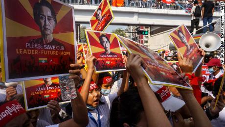 Protesters hold signs featuring Aung San Suu Kyi as they take part in a demonstration against the military coup in Yangon on February 22.