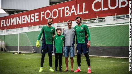 Liverpool goalkeeper Alisson (R) and brother Muriel (L) with father Jose Becker (2-R).