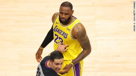 NBA official Mousa Dagher looks over at a fan courtside as he stands in front of James.