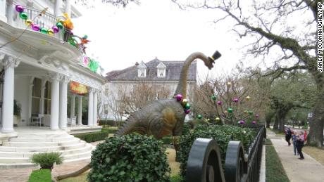 Passersby look at dinosaur figures at a mansion on St. Charles Avenue.