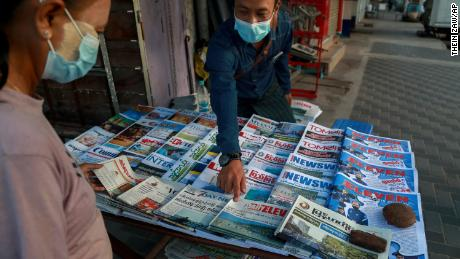 A newspaper seller points at a front-page of a newspaper in Yangon, Myanmar, Febuary 2, 2021.