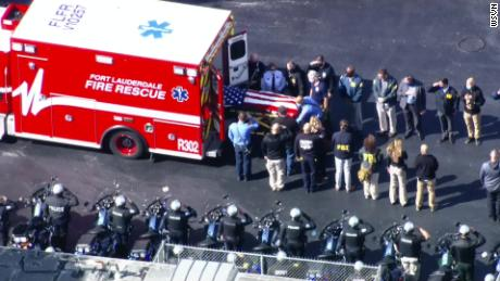 A body draped in an American flag is transported from an ambulance following the fatal shooting of two FBI agents in Sunrise, Florida, on Tuesday.