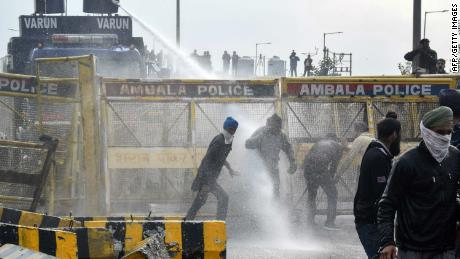 Police block a road and use a water cannon to disperse farmers marching to India's capital, New Delhi, on the outskirts of Ambala on November 26, 2020.