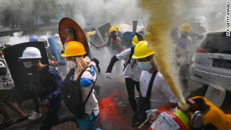 A protester uses a fire extinguisher as others holding homemade shields run during a demonstration in Yangon on Wednesday.