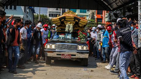 People pay respects as the hearse carrying the coffin of Ma Kyal Sin drives on the street.