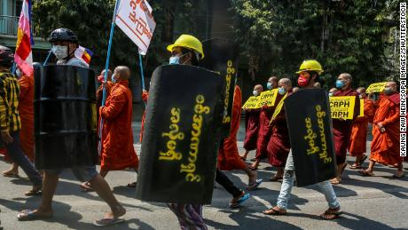 Demonstrators carry placards and makeshift shields during a protest against the military coup in Mandalay, Myanmar, March 7.