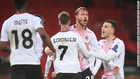 Kjaer celebrates with teammates Samu Castillejo and Diogo Dalot after scoring their team's goal against Manchester United.