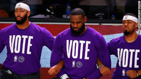 Anthony Davis, LeBron James  Quinn Cook of the Los Angeles Lakers kneel during the National Anthem with VOTE shirts on.